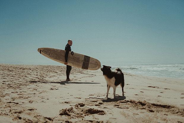 Dimitar Atanasov with a surfboard on the beach